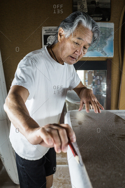 Venice Beach, CA, USA - May 10, 2016: Man in his workshop shaping a surfboard