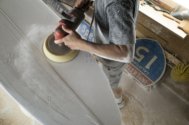Man buffing a surfboard in his workshop