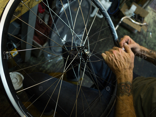 Man repairing spokes on a bike wheel in his workshop
