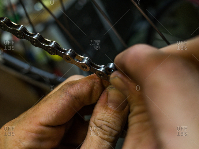Man adjusting chain on a bicycle in his workshop