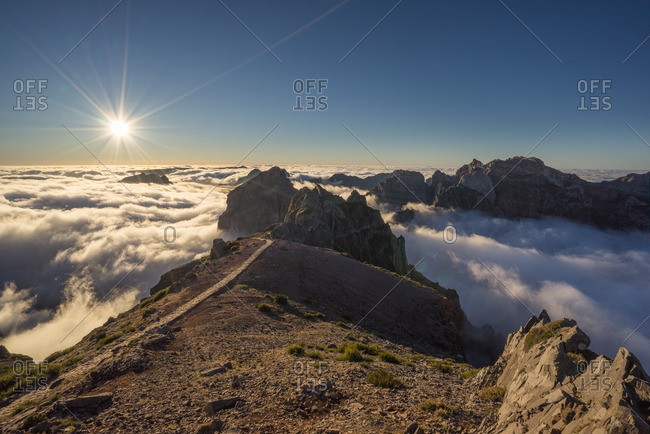Sun shining above the clouds and peaks of the Pico do Arriero in Madeira, Portugal