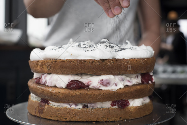 Woman sprinkling poppy seeds onto cake