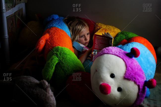 Girl curled up with a stuffed caterpillar and a book