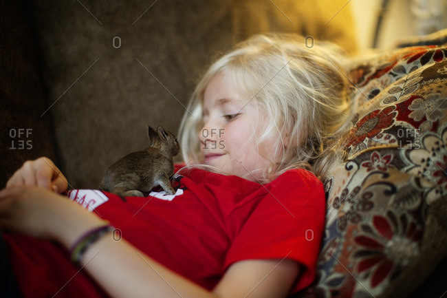 Girl cuddling on sofa with baby rodent