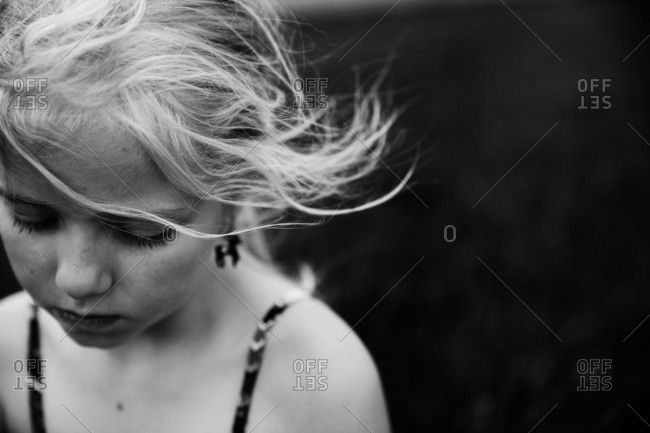 Portrait of a blonde girl looking down in black and white