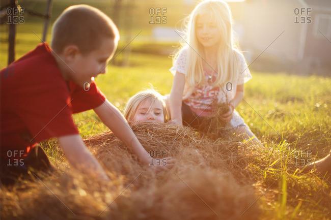 Children burying little girl in pile of hay