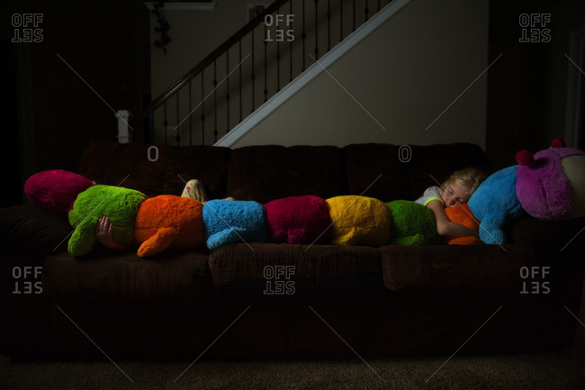 Girl napping with a stuffed caterpillar on a sofa