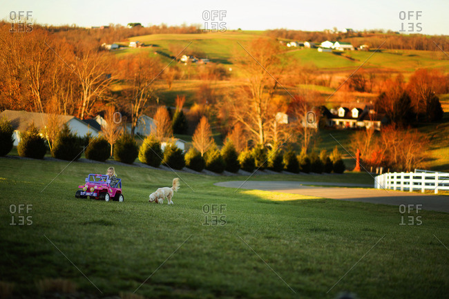 Girl riding in toy car while dog follows in a country field