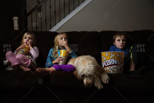 Three children watching a movie with popcorn