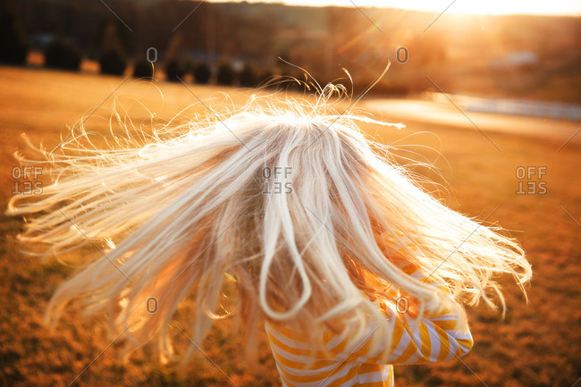 Blonde haired girl twirling in the sunlight