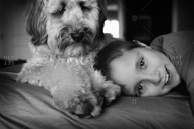 Boy lying next to his dog