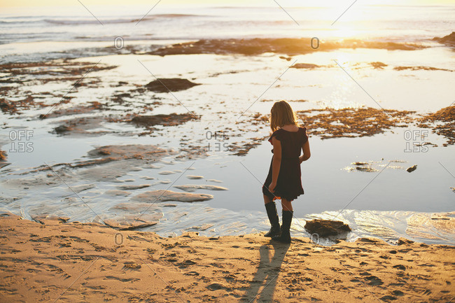 Girl walking along the beach and looking at the water