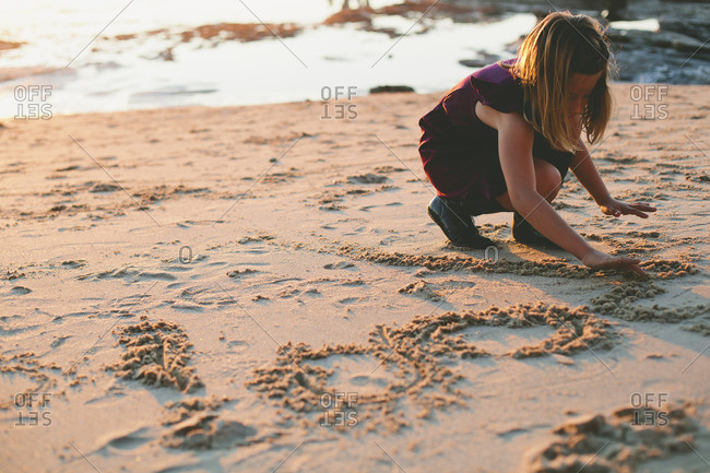 Girl writing in the sand at the beach