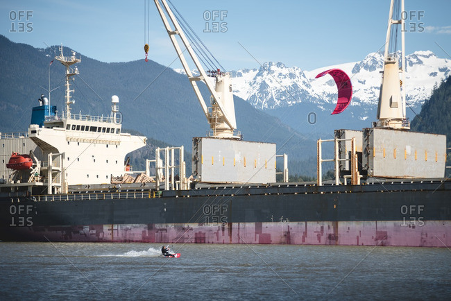 Person kite boarding in front of a boat in Squamish Spit, British Columbia