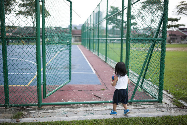 Toddler walking on to an athletic court at a local park