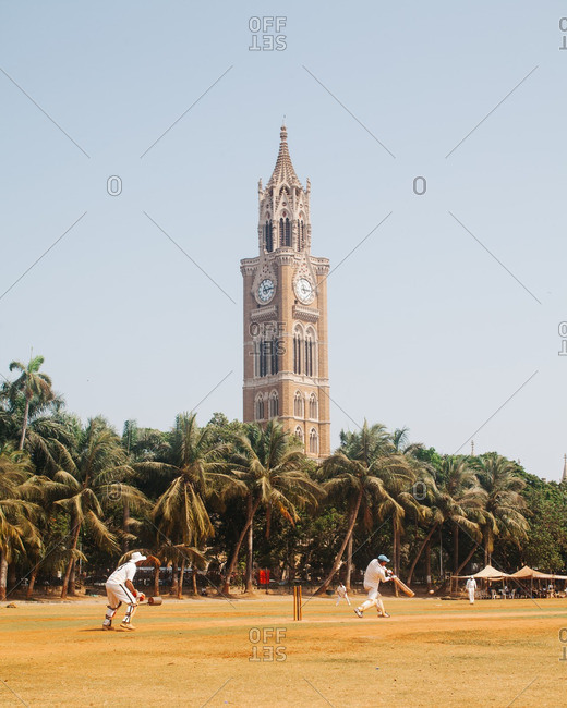 Cricket match near a clock tower
