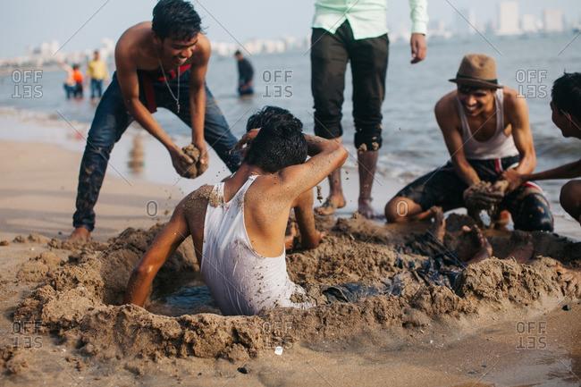 Mumbai, India - April 2, 2016: Teens playing in sand, Mumbai