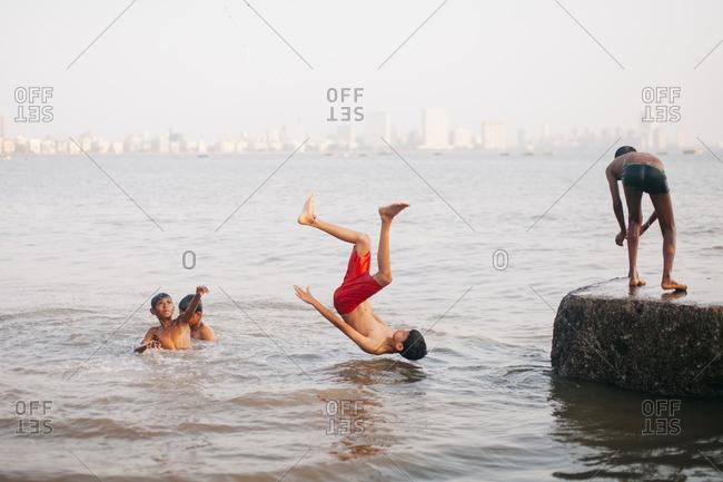 Mumbai, India - April 2, 2016: Boys diving into ocean, Mumbai