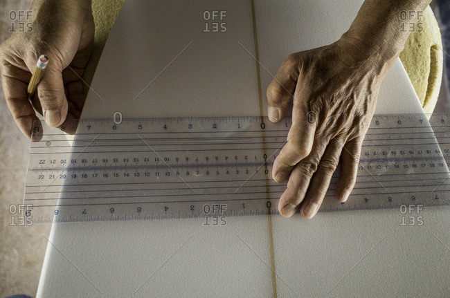 Craftsperson using a wide ruler to take a measurement