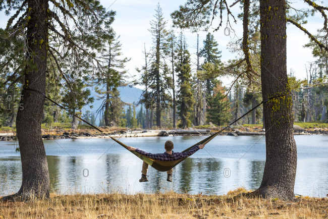 Man relaxing in a hammock on the shore of Bull Lake, California