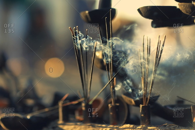 Sticks of incense burning on a stone wall