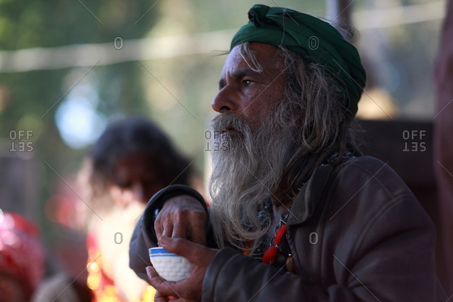 Pakistan - March 31, 2014: Senior man in Pakistan dipping his fingers into a ceramic bowl