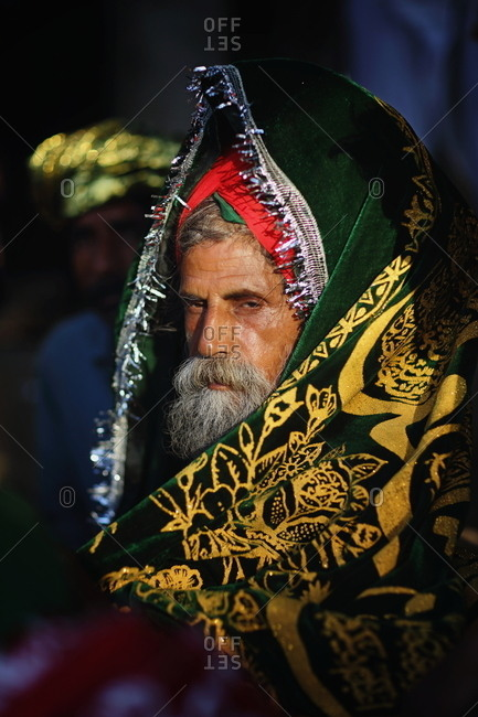 Pakistan - March 31, 2014: Senior man wrapped in a yellow and green shawl