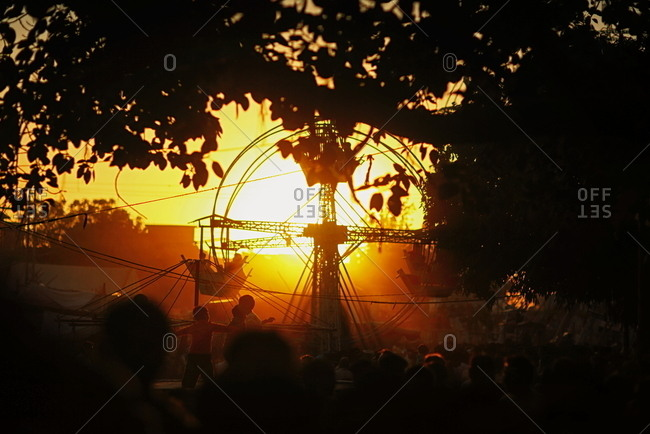 Pakistan - March 31, 2014: Simple ferris wheel and a crowd at sunset in a Pakistan square