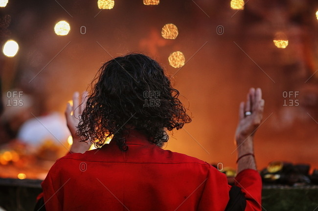 Man in a red jacket raising his hands in prayer