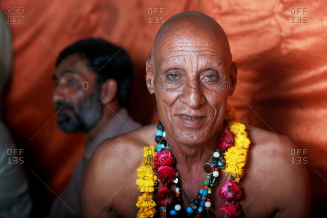Pakistan - March 30, 2014: Senior bald man with beaded necklaces and flower garland