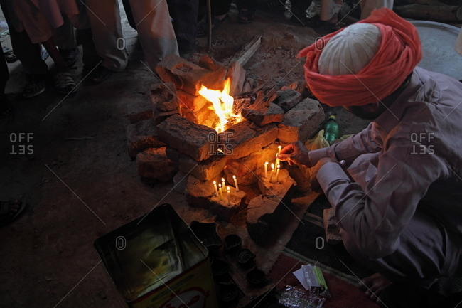 Man in a turban placing small candles around a brick fire pit