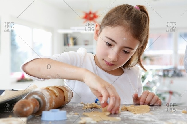 Girl looking down rolling out dough cookie dough