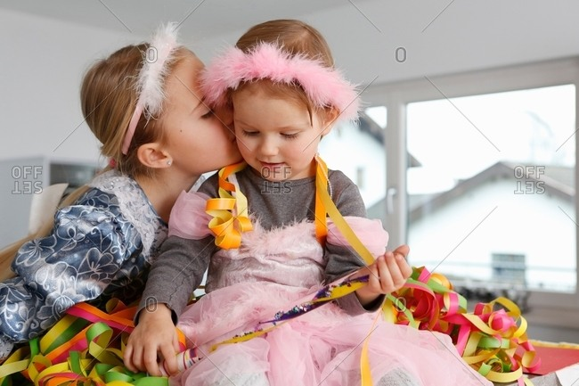 Sisters dressed up as princesses, covered in party streamers, kiss on cheek