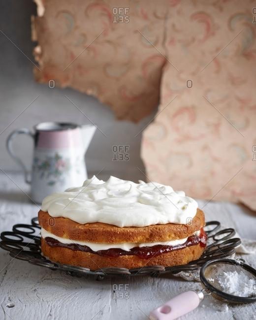 Iced sponge custard cake on vintage dish