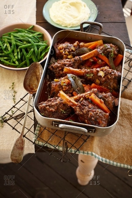 Overhead view of lamb shank stew in roasting tin with green beans and mashed potato