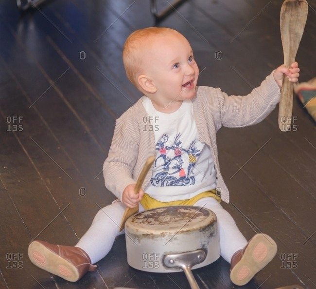 Toddler banging saucepan with kitchen utensils