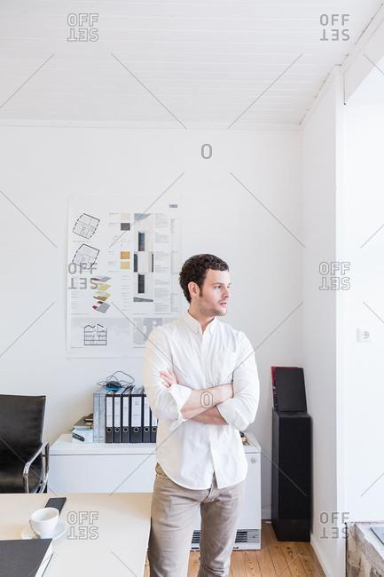 Mid adult man in office arms crossed looking sideways through window