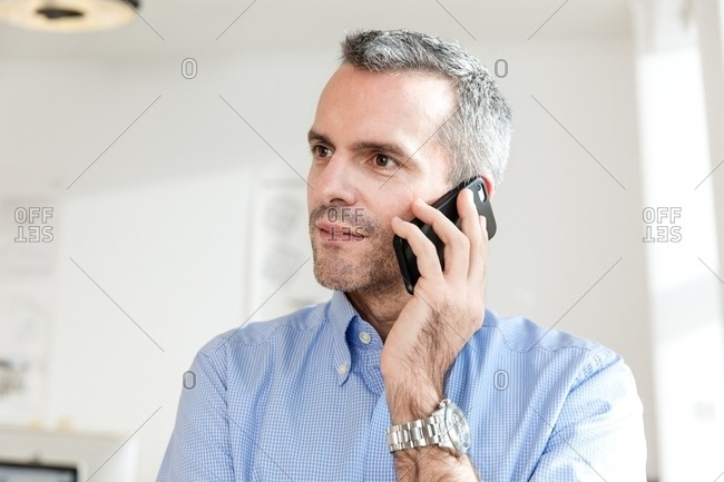 Mature man using smartphone to make telephone call looking away