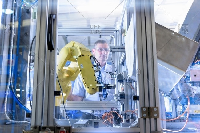 Engineer with robot in automotive parts factory