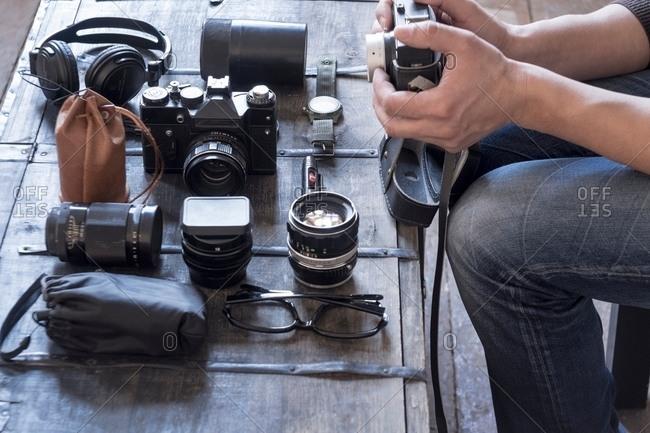 Photographer preparing camera and accessories at desk
