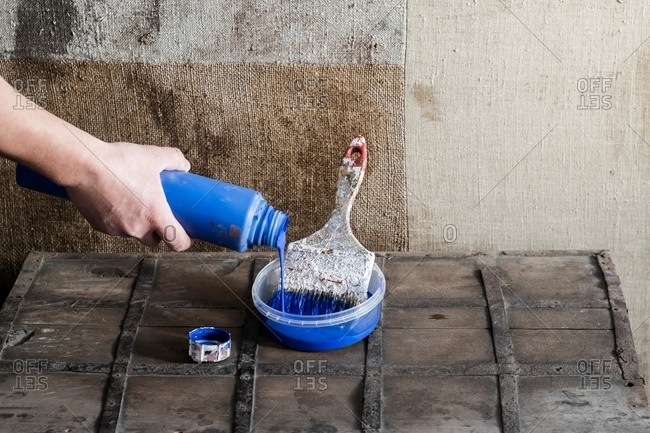 Hand pouring paint into plastic container with paint brush