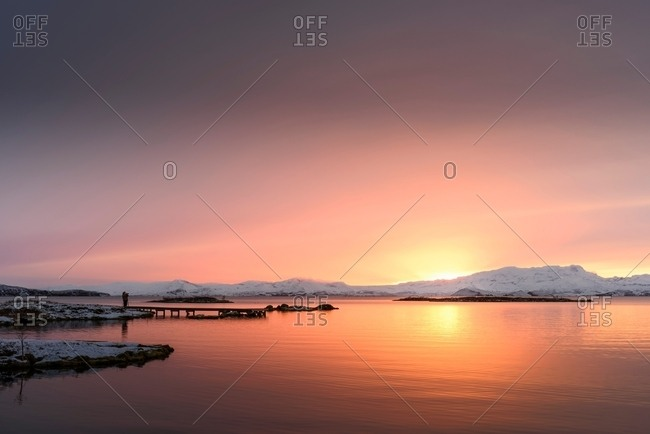 Man standing on pier by lake looking at snow covered mountain at sunset, Thingvellir, Iceland