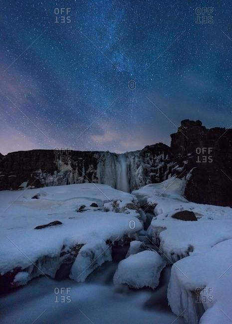 Icy snow covered landscape underneath starry night sky, Thingvellir, Iceland