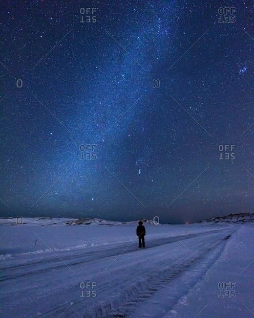 Man on snow covered landscape underneath starry night sky, Kleifarvatn, Iceland