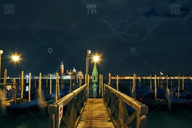 Pier and distant view of Church of San Giorgio Maggiore at night, Venice, Italy