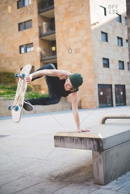 Young male skateboarder doing balance skateboard trick on urban concourse seat