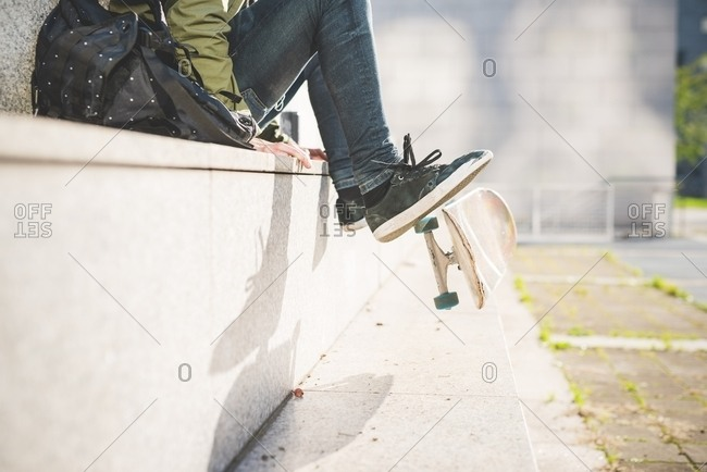 Waist down view of young male urban skate boarder sitting on wall flipping skateboard with feet