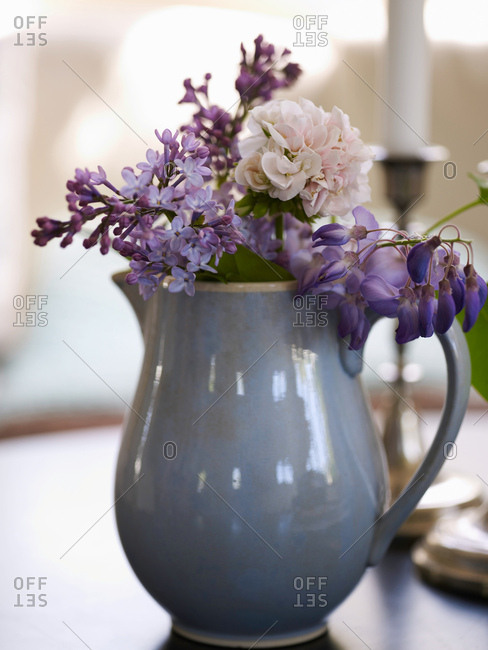 Vase of purple flowers on table
