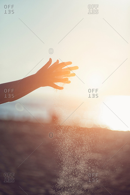 Girls hands sprinkling sand on beach at sunset