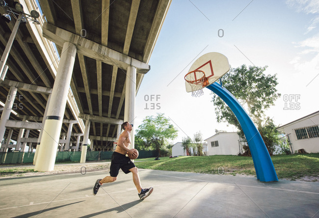 Side view of young man holding basketball running to basketball hoop